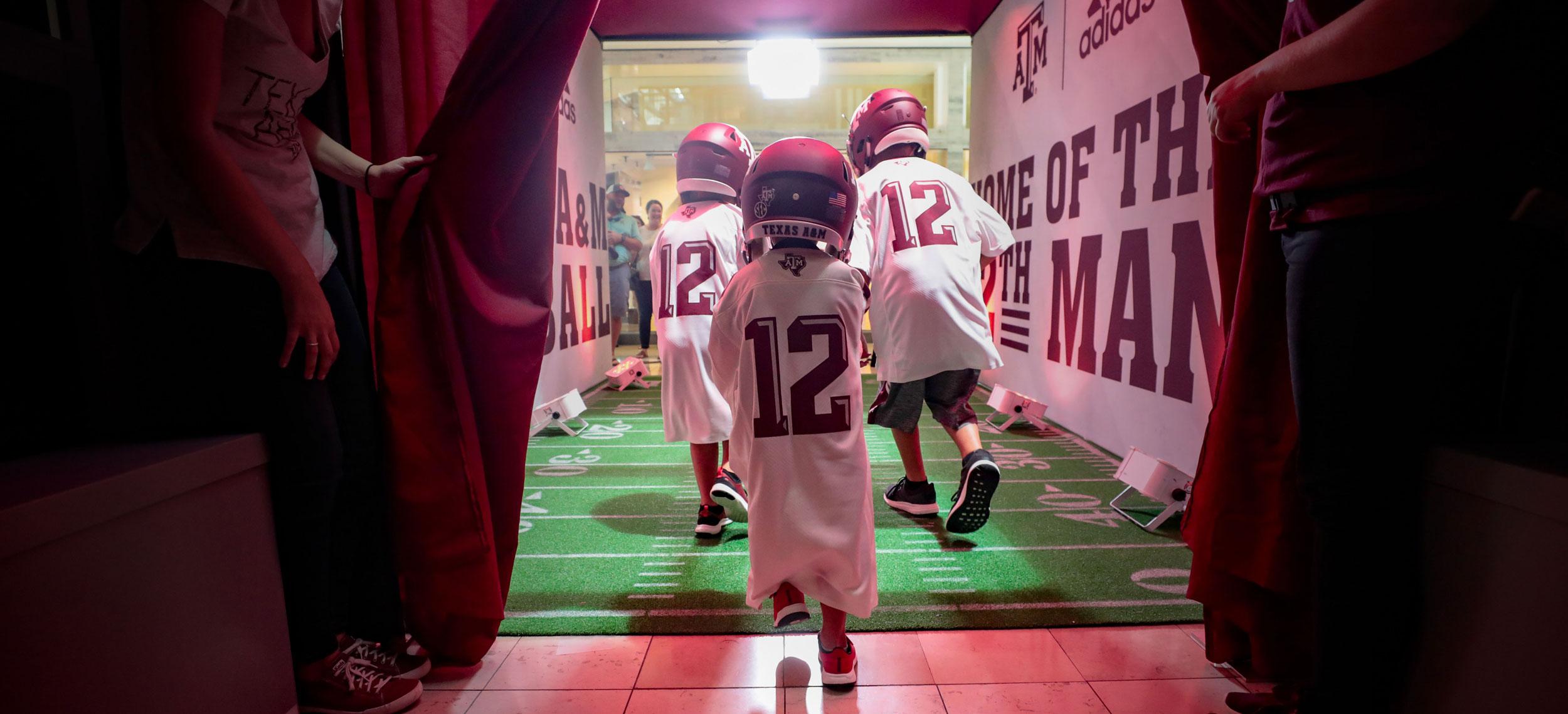 kids running through a pop-up, mock bull pen with tamu football jerseys
